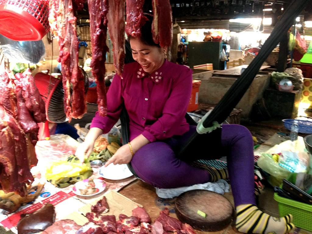 Šťastná paní na tržnici ve městě Kampot, Kambodža
