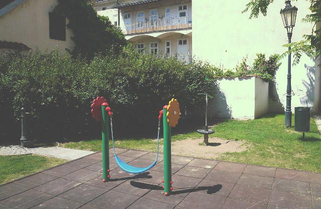 Dětské hřiště na malé ulici Za haštalem. Vlevo můžete vidět klasické litinové pítko.
